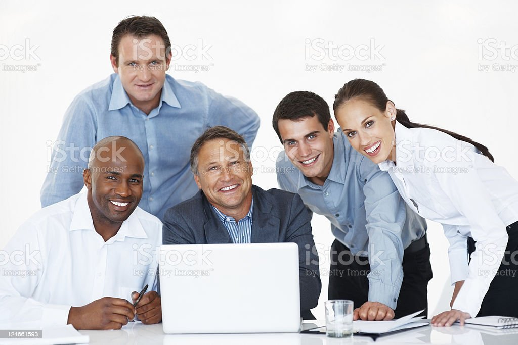 Smiling business team using laptop royalty-free stock photo