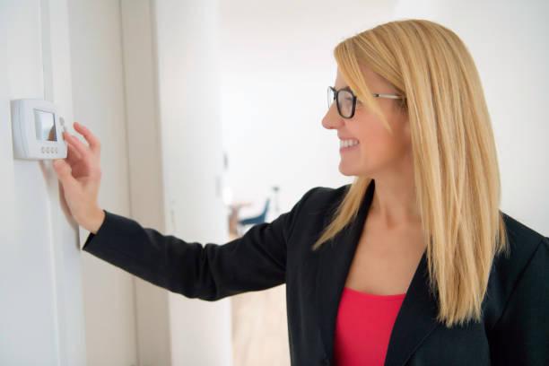 Eine lächelnde Geschäftsfrau, die Thermostat auf Hausheizung spasst – Foto