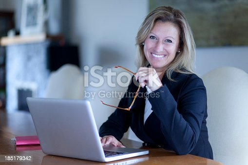 istock A smiling business woman at a desk using a laptop 185179342