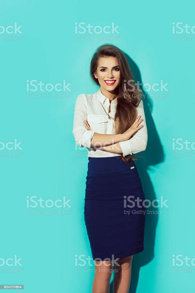 Smiling business woman , crossed arms. Young model. on blue background. stock photo
