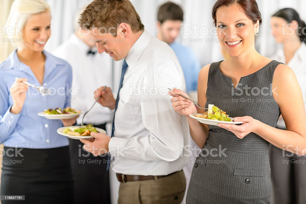 Smiling business woman during company lunch buffet stock photo