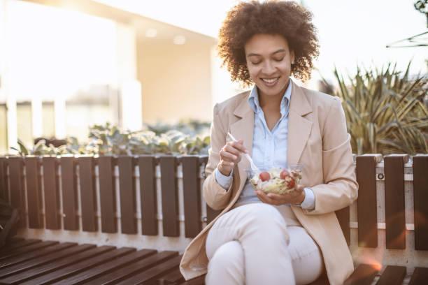 Lächelnde Geschäftsfrau isst einen Gemüsesalat im Freien – Foto