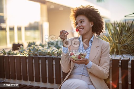 Smiling mixed race business woman eating a vegetable salad outdoors