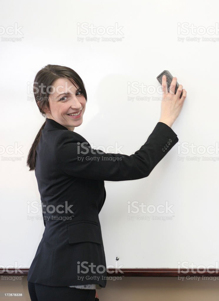 A smiling business woman erasing a whiteboard. stock photo