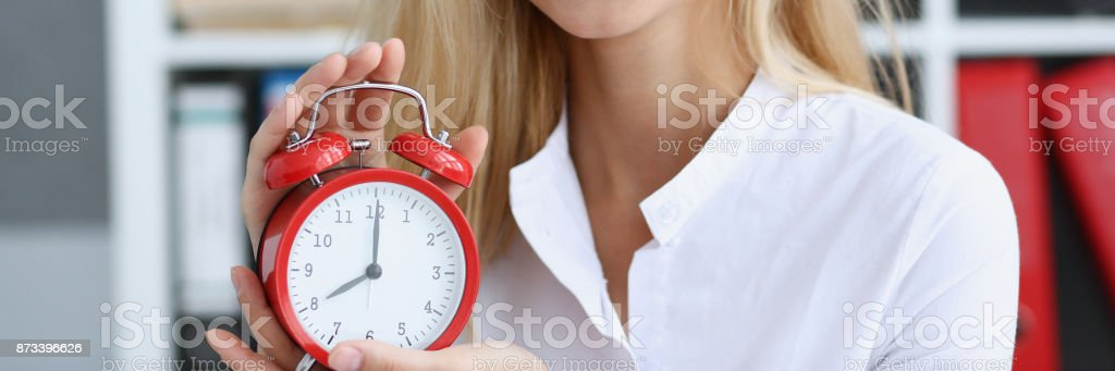 Smiling business woman holding in hand on the alarm clock a red color...