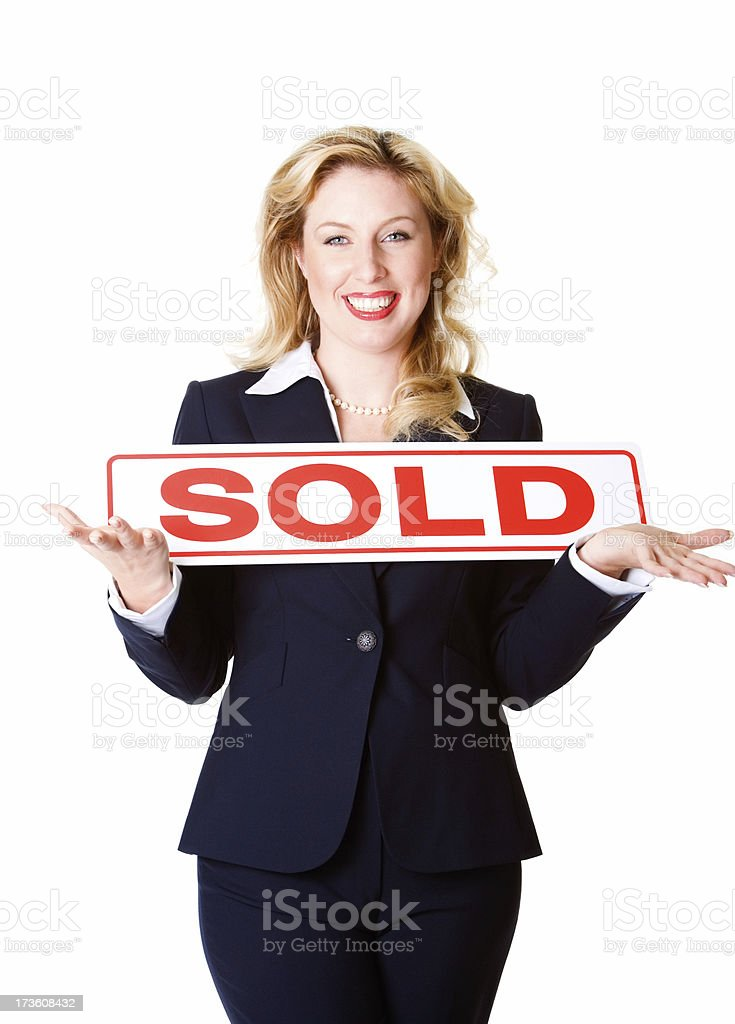 Smiling business woman holding up SOLD sign royalty-free stock photo