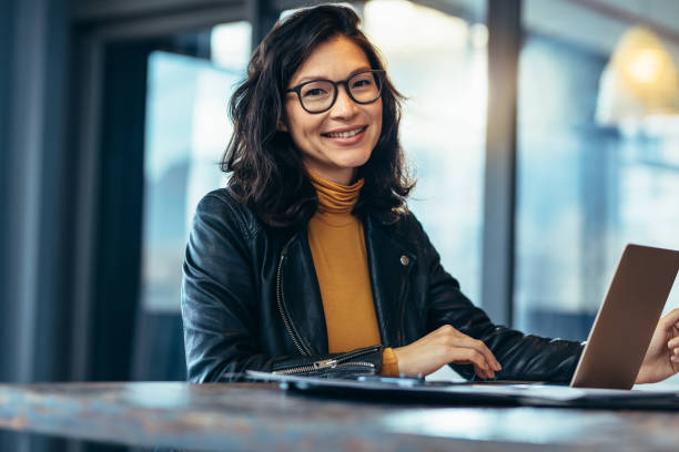 Smiling business woman in casuals at office Portrait of attractive business woman sitting at her desk with laptop computer in office. Smiling business woman in casuals at office. east asian ethnicity stock pictures, royalty-free photos & images