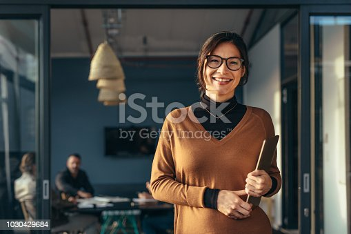 Portrait of positive female executive holding a laptop standing in office with colleagues working in background. Smiling business woman in casuals at office.