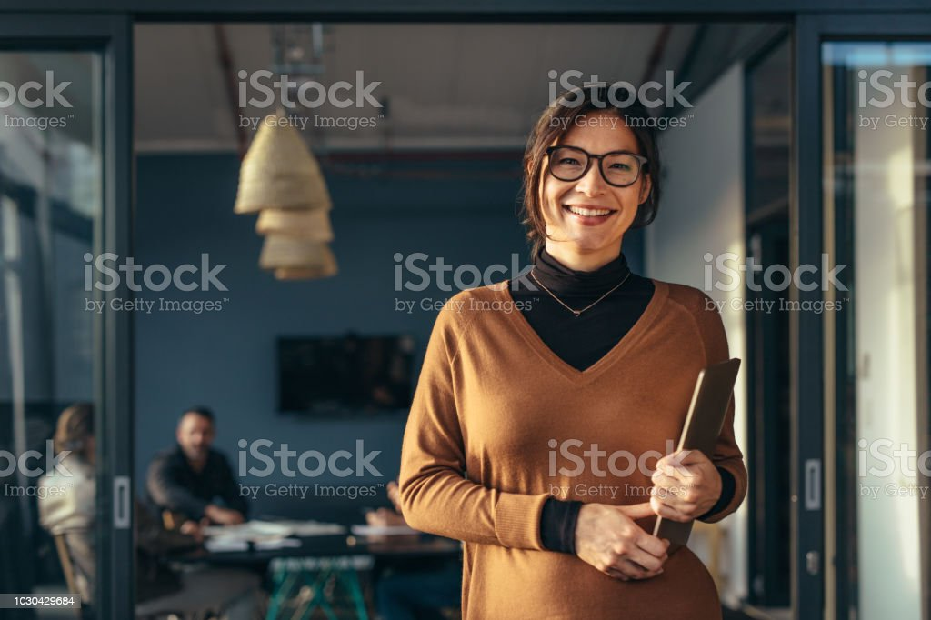 Smiling business woman in casuals at office stock photo