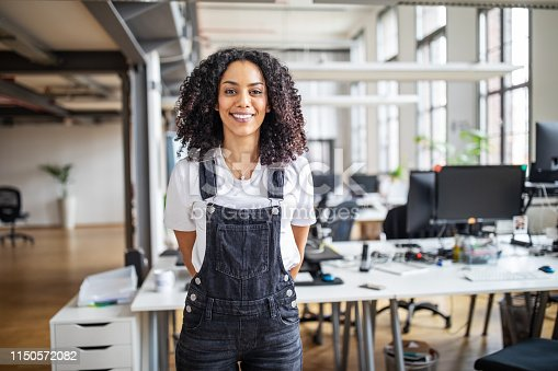 Portrait of mature african american businesswoman in casuals standing at her desk. Female professional looking at camera and smiling.