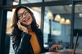 istock Smiling business woman in casuals talking on phone 1030429760