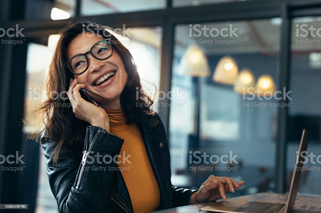 Smiling business woman in casuals talking on phone stock photo