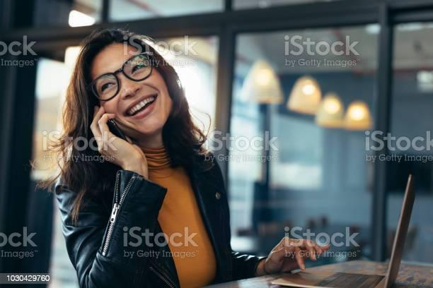 Glimlachende Zakenvrouw In Casuals Praten Over Telefoon Stockfoto en meer beelden van Alleen volwassenen