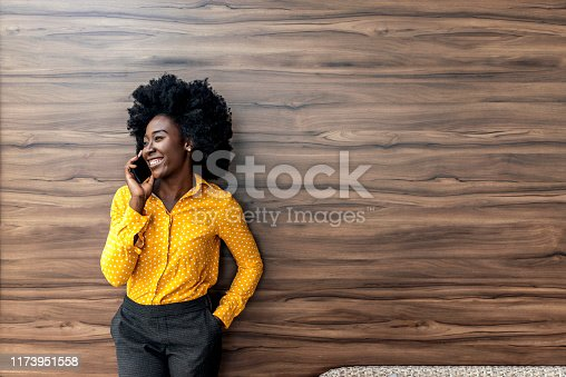 Focused African American millennial woman talking on cellphone or smartphone working consulting client, concentrated smiling female speaking or chatting on smartphone distracted from studying.