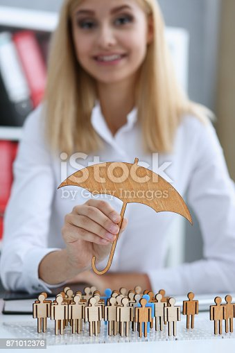 958039576 istock photo Smiling Business woman in hand holds a miniature umbrella 871012376