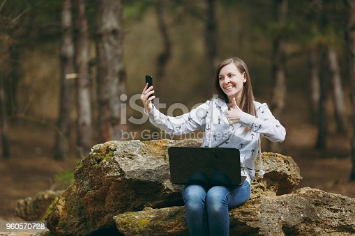 862602714istockphoto Smiling business woman or student sitting on stone with laptop doing selfie and showing thumb up on mobile phone in city park or forest working outdoors on green background. Mobile Office concept. 960570728