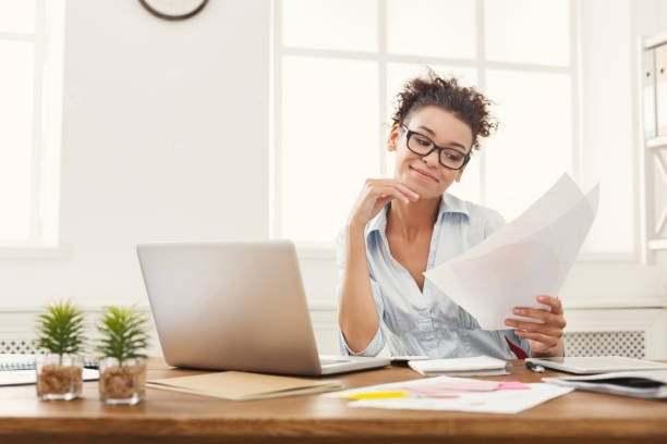 Smiling business woman reading document stock photo