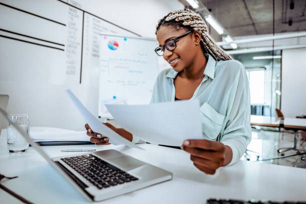 Smiling business woman reads documents, works in a bright office. stock photo