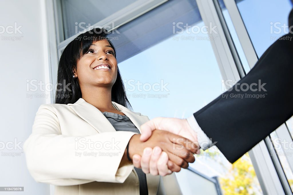 Smiling business woman shaking hand with business man royalty-free stock photo