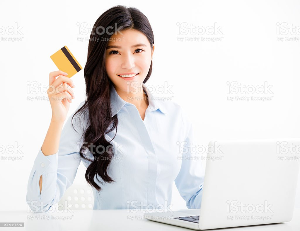 Smiling business woman showing credit card in office stock photo