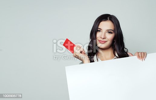 Smiling business woman showing red empty card and holding white blank banner backround. Business, advertising marketing and product placement concept
