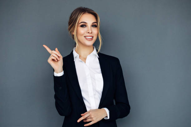 smiling business woman showing something on her hand - finger point stock photos and pictures