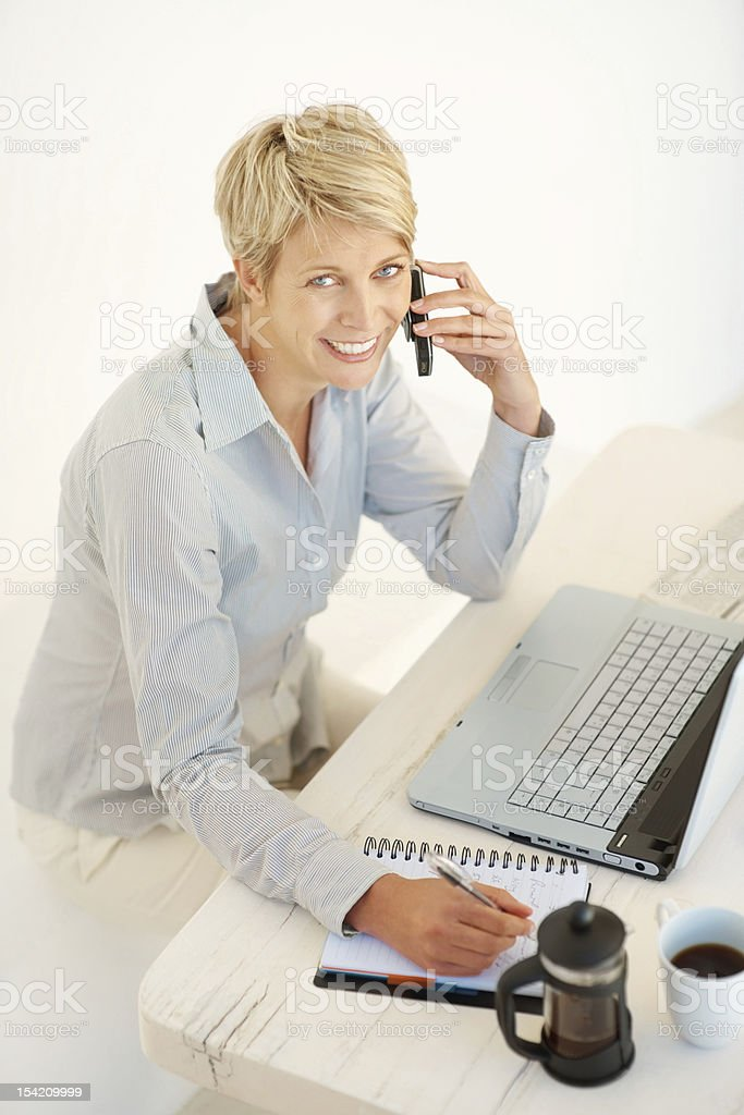 Smiling business woman taking messages and speaking on the phone royalty-free stock photo