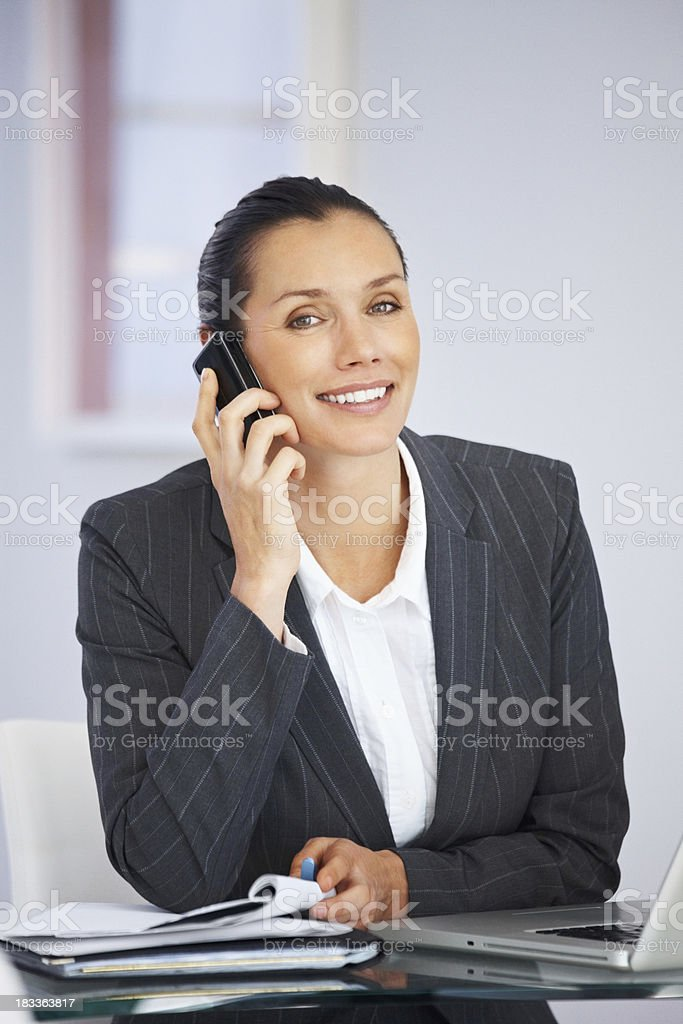 Smiling business woman using a cellphone at work royalty-free stock photo