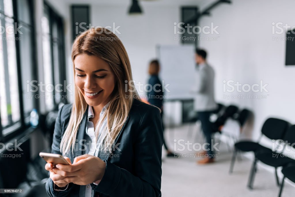 Smiling business woman using phone during a break. Collegues standing in the background stock photo