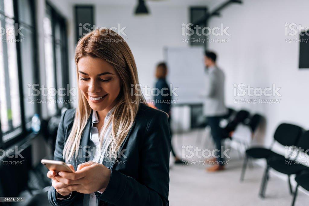 Business-Frau mit Telefon während einer Pause lächelnd. Kollegen stehen im Hintergrund – Foto