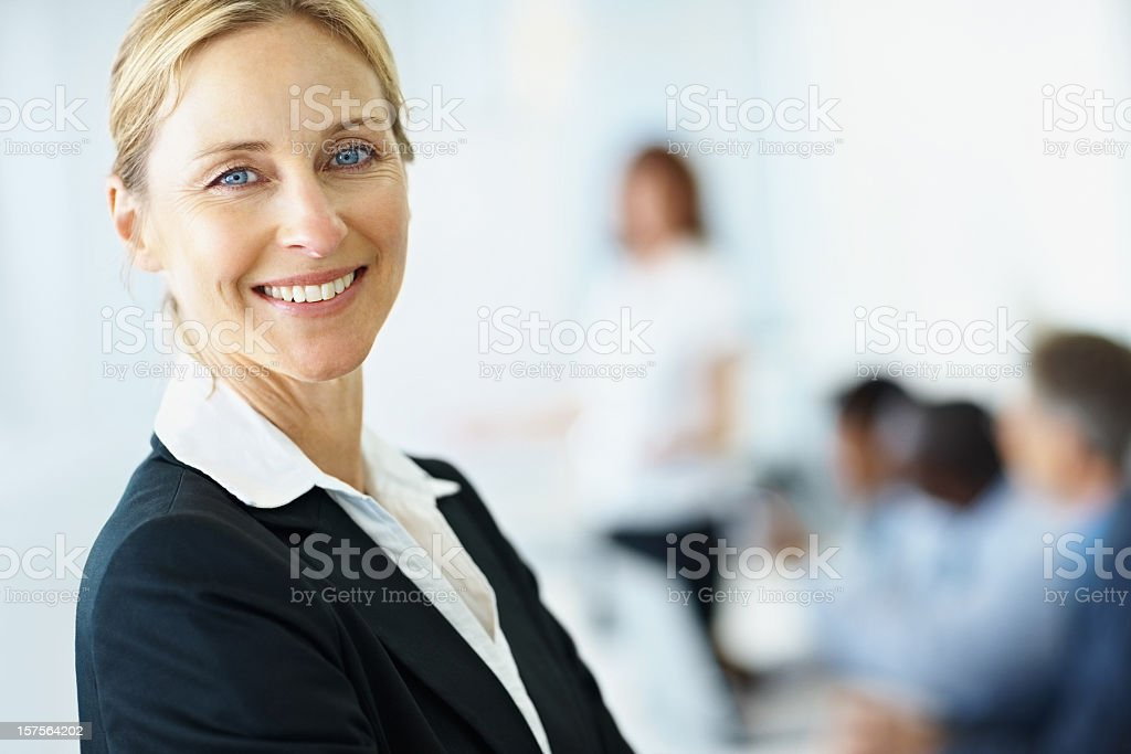 Smiling Business woman with colleagues in background royalty-free stock photo