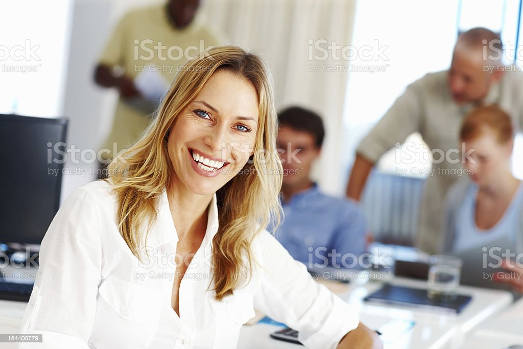 Smiling business woman with executives in the background royalty-free stock photo