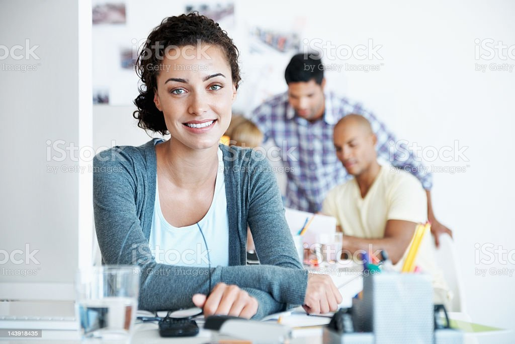 Smiling business woman with team working in background royalty-free stock photo