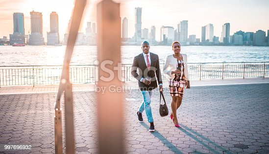 Shot of black businessman and African-American business woman on the go holding coffee cup and digital tablet and smiling in New York City, USA. City and skyscrapers in the back.