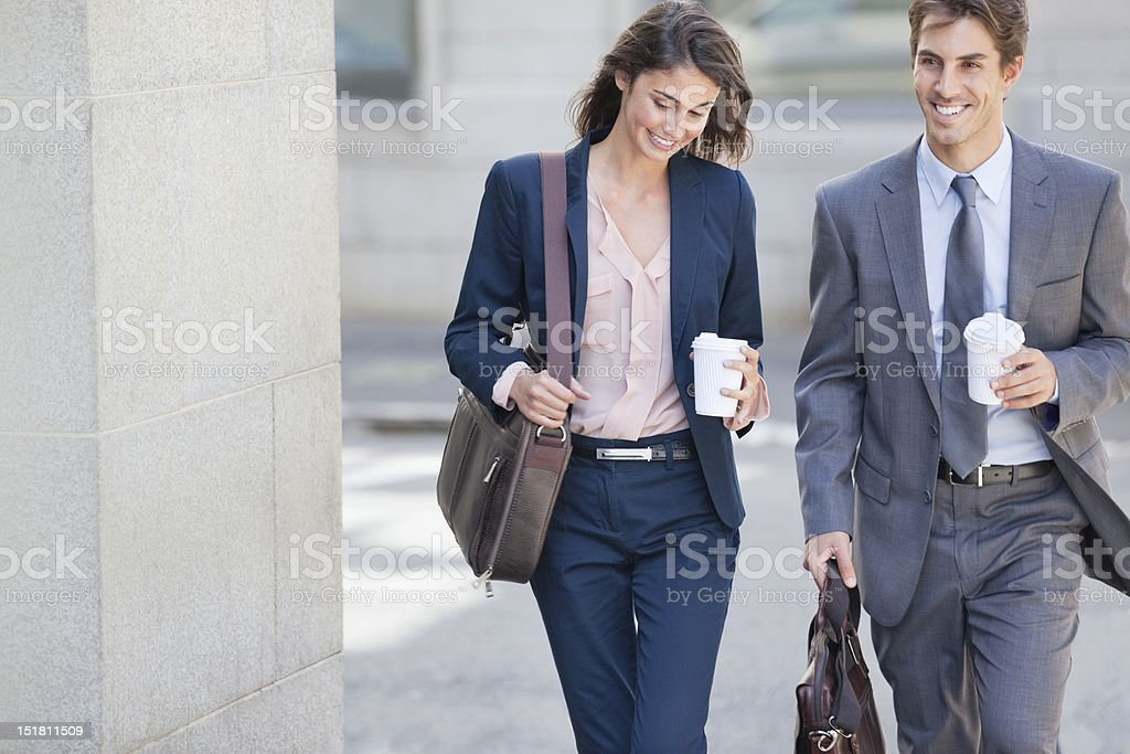 Smiling businessman and businesswoman walking with coffee cups stock photo