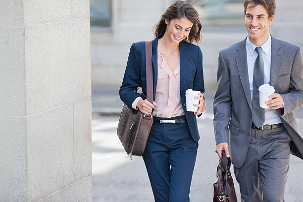 smiling businessman and businesswoman walking with coffee cups - 盛裝 個照片及圖片檔