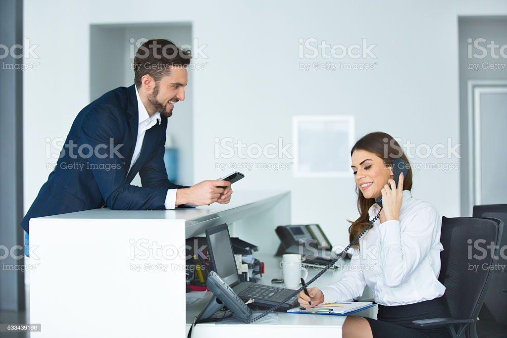 Souriant homme daffaires et femme réceptionniste au secrétaire