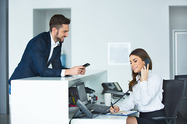 Smiling businessman and female receptionist at the secretary desk. stock photo