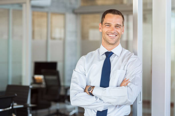 Smiling businessman at office Portrait of cheerful businessman with arms folded standing in conference room. Happy young business man in shirt and tie looking at camera. Portrait of a smiling businessman in modern office with copy space. seller stock pictures, royalty-free photos & images