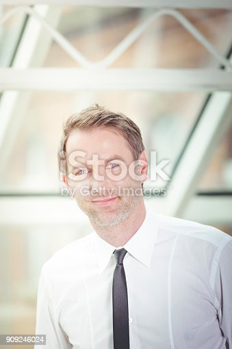 825082848istockphoto smiling businessman at the office 909246024