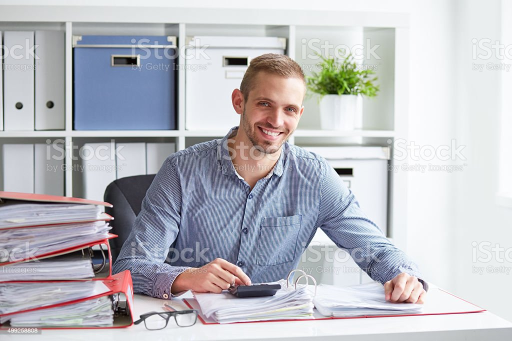 Smiling businessman calculates taxes stock photo