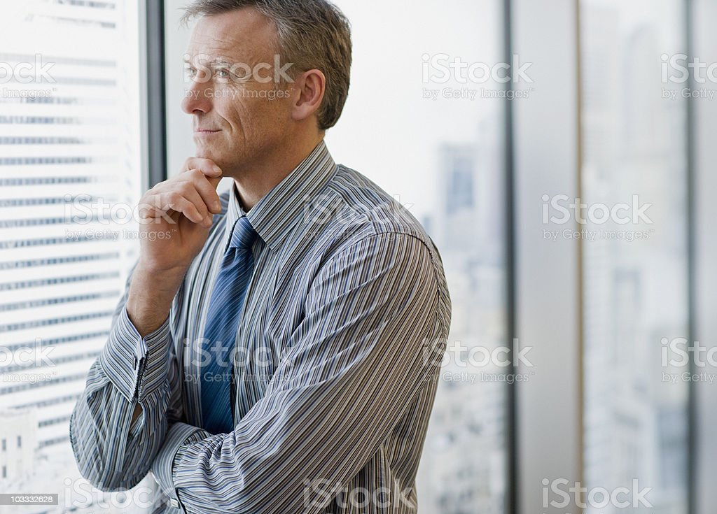 Smiling businessman daydreaming and looking out office window stock photo
