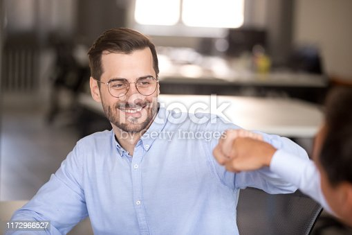 Smiling millennial man give fist bump to male colleague or business partner motivated for shared win or triumph, excited businessman congratulate coworker with good result, celebrating win together