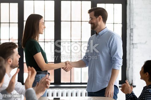 509032417 istock photo Smiling businessman handshake female employee greeting with success 1219224607