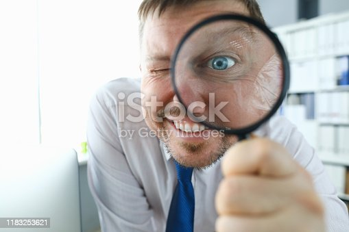 istock Smiling businessman hold magnifying glass 1183253621