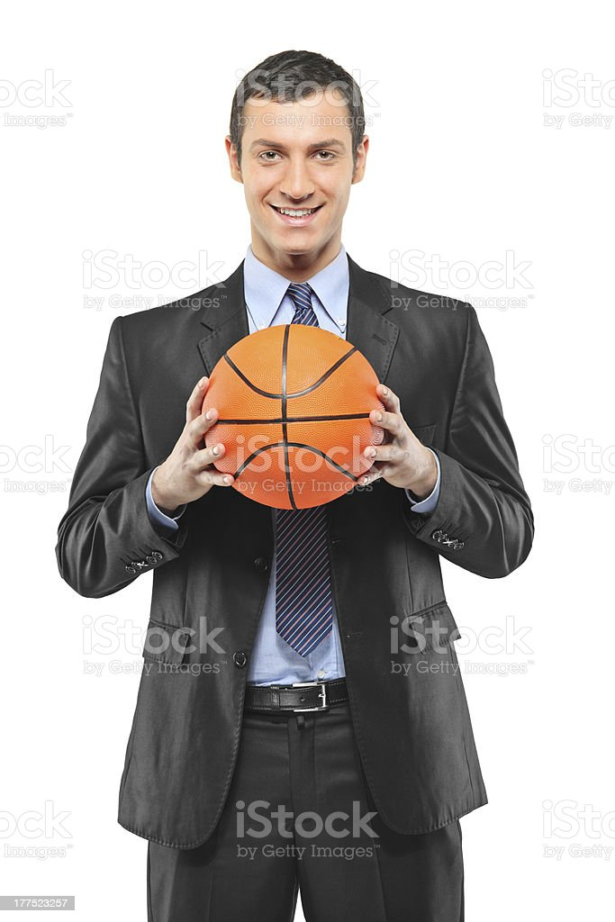 Smiling businessman holding a basketball stock photo