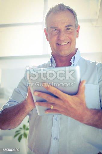 istock Smiling businessman holding digital tablet at office 670902120