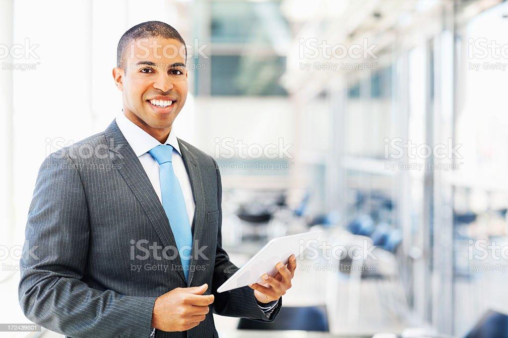 Smiling businessman holding digital tablet stock photo