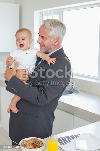 istock Smiling businessman holding his baby in the morning before work 692690648