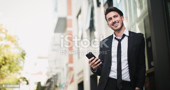 istock Smiling businessman holding his phone 870585468